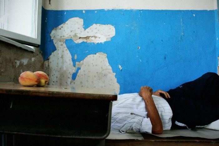 Тбилиси. Беженцы из Гори поселились в местных школах и детских садах. Человек спит на голых партах, а на столе лежит гуманитарная помощь - персики, которых привезли огромное количество вместо матрасов и предметов первой необходимости