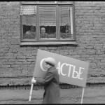 24_vladimir-sokolaev-zhenshchina-speshashchaya-na-pervomaiskuyu-demonstraciyu.-ulica-obnorskogo.-novokuzneck.-1.05.1983
