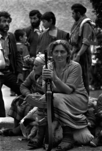 Armenian woman with family and Kalashnikov. Karabakh, Armenia, Soviet Union, (1991). Photo by Oleg Klimov